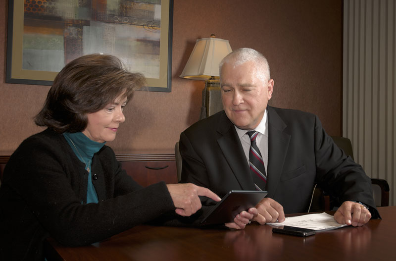 Photo of Dick Heidgerd meeting with a female client to discuss a case.